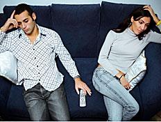 זוג אחרי מריבה יושבים על ספה כחולה