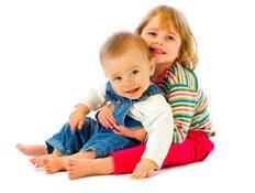 ילדה בחולצת פסים מחבקת תינוק באוברול ג'ינס