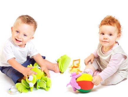 תינוקת ג'ינג'ית ותינוק בלונדיני יושבים ומשחקים בצע (צילום: istockphoto)