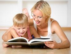 אם ובנה שוכבים על רצפת עץ וקוראים בספר