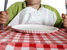 ילד יושב בשולחן עם מפה משובצת מחזיק סכין ומזלג