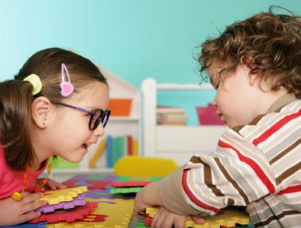 ילדה עם משקפיים מתגרה בילד מתולתל (צילום: istockphoto)