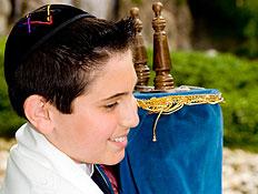 חתן הבר מצווה מחזיק ספר תורה