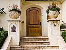 כניסה מרשימה לבית, עם דלת מעץ ועציצים