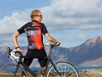 גבר ליד אופניים מסתכל על הר