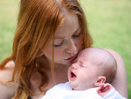 אשה ג'ינג'ית מחזיקה את התינוק שלה בפרצוף עצוב(istockphoto)