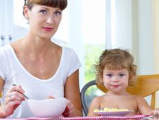 ילד אוכל ואמו לידו