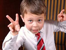 ילד בחליפה מסמן וי בידיו