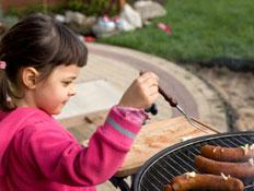 ילדה ליד מנגל עם נקניקיות