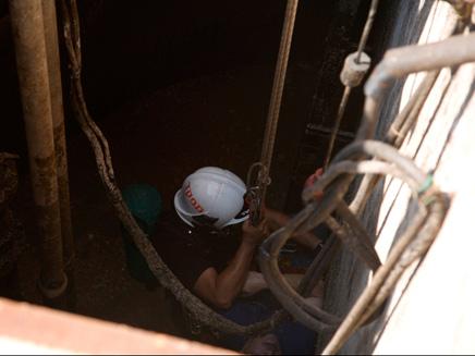 """אדם חולץ מנחל מלא במי ביוב בת""""א (צילום: שירותי כיבוי והצלה, גליל מערבי)"""