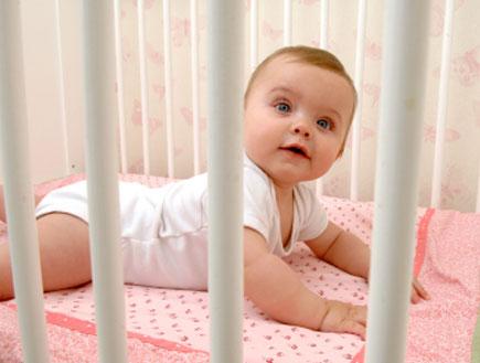 תינוקת עירנית בעריסה
