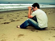 גבר יושב על שפת הים