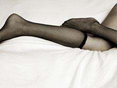 רגליים של אישה עם גרביוני רשת על מיטה