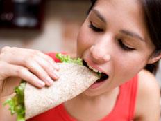 בחורה אוכלת פיתה מגולגלת עם חסה