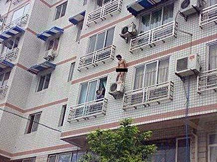 איש ערום מאיים לקפוץ מהבניין (צילום: הסאן)
