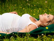 אישה בהריון על הדשא