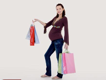 אישה בהריון עם שקיות ביד (צילום: istockphoto)