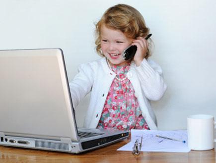 ילדה מדבת בטלפון מול המחשב