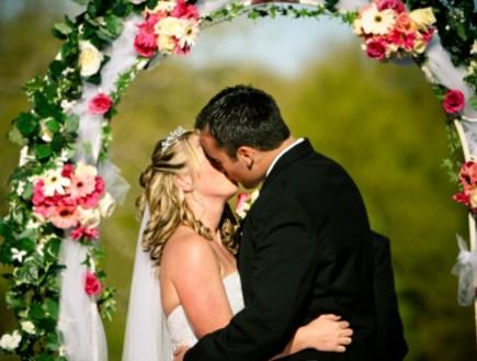 חתן וכלה מתנשקים בחופה