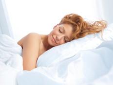 אישה עירומה במיטה