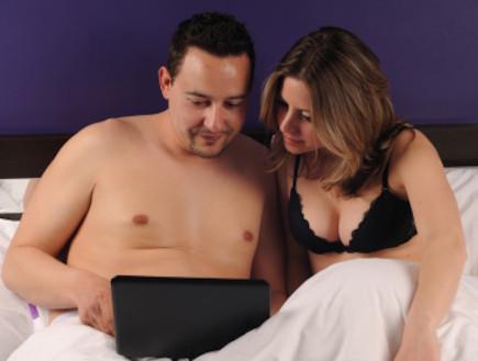 זוג במיטה עם לפטופ (צילום: istockphoto)
