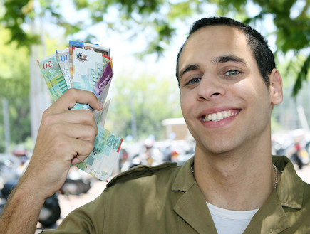 חייל צנחנים מחזיק שטרות ביד מחייך
