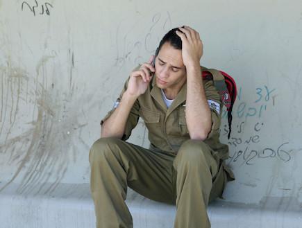 """חייל מדבר בטלפון מיואש בתחנת אוטובוס (צילום: עודד קרני ,פז""""ם)"""