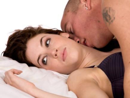 אישה עם גבר במיטה מסתכלת הצידה (צילום: istockphoto)