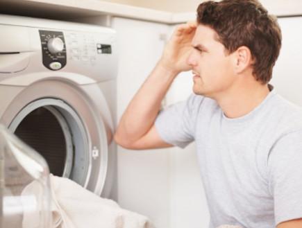 גבר מסתכל על מכונת הכביסה בתסכול (צילום: istockphoto ,istockphoto)