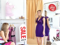 בחורה מודדת בגדים בחנות בגדים