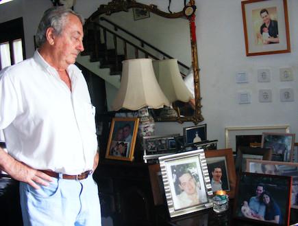 צבי לוינהר בביתו לצד תמונות בניו