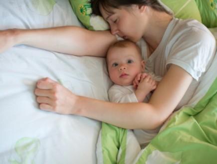 תינוק ער ואמא ישנה לידו במיטה (צילום: istockphoto ,istockphoto)
