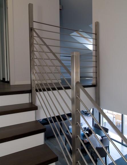 מעקה נירוסטה לצד מדרגות עץ בפנטהאוז בקווים נקיים