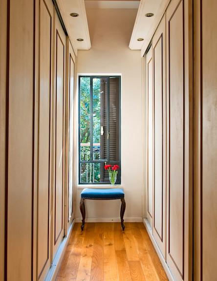 חדר ארונות מקבילים, עם דלתות הזזה, בקצה דרגש לישיבה ולהנחת בגדים.