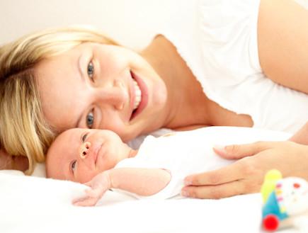 תינוק שוכב לצד אמא מחייכת (צילום: אימג'בנק / Thinkstock)