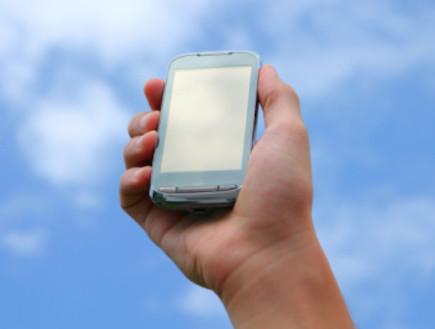 יד מחזיקה טלפון סלולרי על רקע שמיים  (צילום: אימג'בנק / Thinkstock)