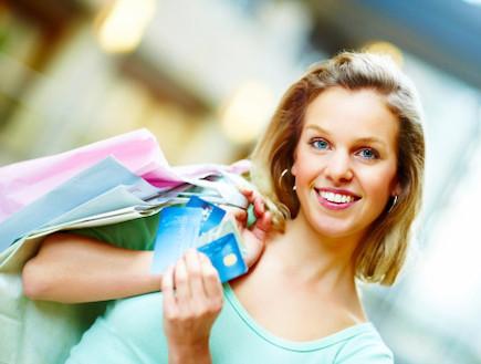 אישה מחזיקה כרטיסי אשראי ושקיות