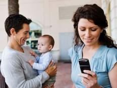 אמא מסתכלת על הטלפון ואבא וילדה ברקע (צילום: אימג