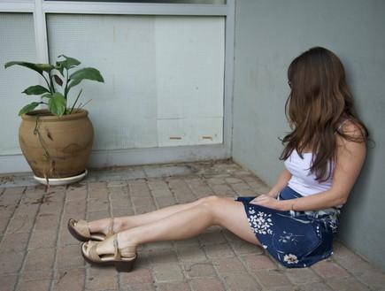 נערה בדיכאון  יושבת על הרצפה