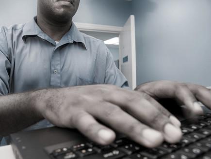 איש ללא פנים מקליד על מחשב