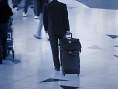 איש סוחב מזוודה בשדה התעופה