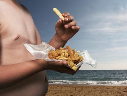 ילד שמן בחוף הים (צילום: getty images)