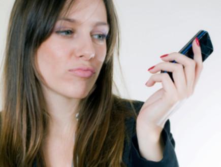 אישה מסתכלת על טלפון סלולרי