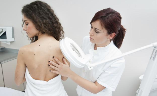רופאה בודקת גב של אישה  (צילום: thinkstock ,thinkstock)