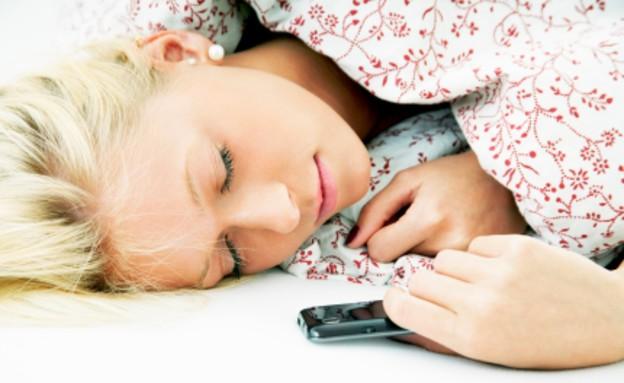 אישה ישנה עם טלפון סלולרי (צילום: istockphoto)