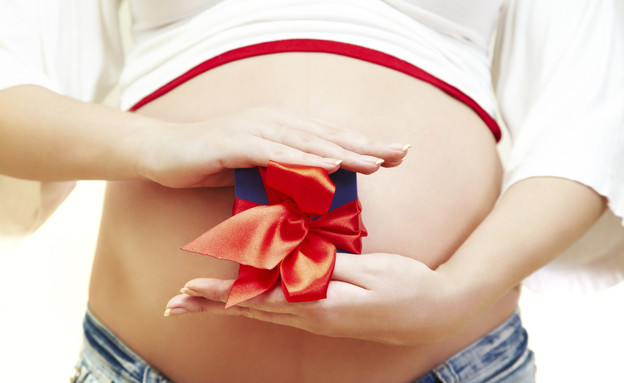 בטן של אישה בהריון עטופה בנייר מתנה (צילום: אימג'בנק / Thinkstock)