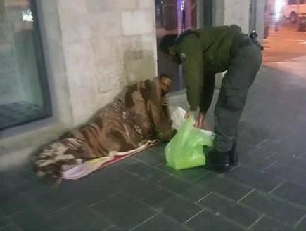 שוטר מגב נותן אוכל להומלס (צילום: מתוך