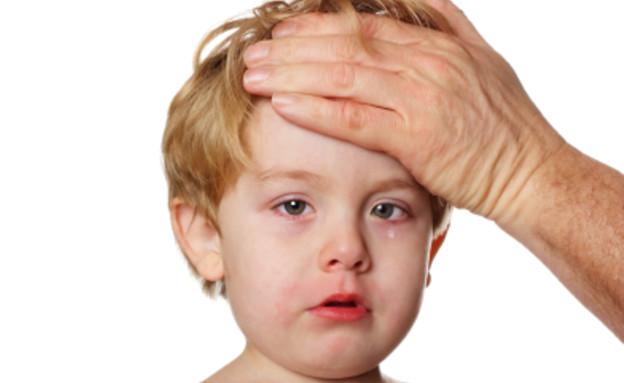יד גברית על מצח של ילד בלונדיני בוכה וחולה (צילום: istockphoto ,istockphoto)