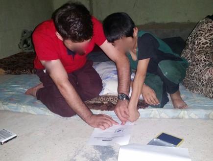ילדים יזידים חותמים בטביעת אצבע כדי לאמת את זהותם