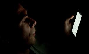 איש עם סמארטפון בחדר חשוך (צילום: http://www.japanexperterna.se ,Flickr)